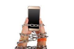 Manos encadenadas que sostienen un smartphone Imagen de archivo libre de regalías
