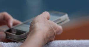 Manos envejecidas de una mujer que birla su teléfono móvil almacen de video