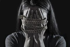 Manos envueltas en la cara de la cubierta de la cinta de la medida del sastre de la nutrición sufridora SID de la anorexia o de l Imagenes de archivo