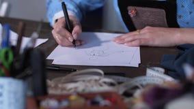 Manos expertas de la modista de la mujer que crean bosquejo almacen de metraje de vídeo
