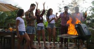 Manos felices de cocinar alegres del aumento del grupo de Frineds de la barbacoa de la gente joven que recolectan en la terraza d almacen de video