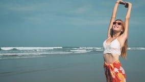Manos felices del estiramiento de la muchacha en la playa metrajes