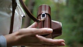 Manos femeninas agradables que juegan con una cámara marrón en un bosque verde en el slo-MES metrajes
