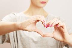Manos femeninas bajo la forma de corazón Foto de archivo libre de regalías