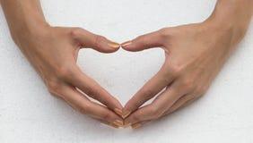 Manos femeninas bajo la forma de corazón imagen de archivo