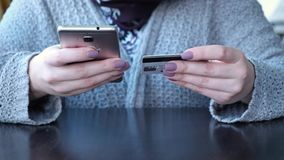 Manos femeninas caucásicas jovenes que compran mercancías de Internet en su smartphone con su tarjeta de crédito metrajes