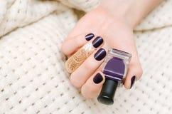 Manos femeninas con diseño púrpura oscuro del clavo Imagen de archivo