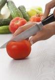 Manos femeninas con el cuchillo, cortando los tomates Fotos de archivo