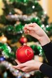 Manos femeninas con el juguete de la Navidad Foto de archivo libre de regalías