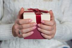 Manos femeninas con el pulimento de clavos del color de los rosas bebés en los fingeres que sostienen la caja de regalo roja imagen de archivo