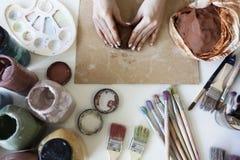 Manos femeninas con la arcilla Fotos de archivo libres de regalías