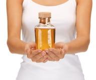 Manos femeninas con la botella de aceite Imagen de archivo libre de regalías