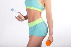 Manos femeninas con la botella de agua y de pesa de gimnasia Foto de archivo libre de regalías