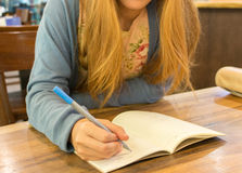 Manos femeninas con la escritura de la pluma en el cuaderno Fotografía de archivo