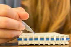 Manos femeninas con la escritura de la pluma en el cuaderno Imágenes de archivo libres de regalías