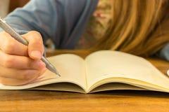 Manos femeninas con la escritura de la pluma en el cuaderno Foto de archivo libre de regalías