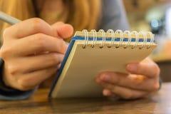 Manos femeninas con la escritura de la pluma en el cuaderno Imagen de archivo libre de regalías