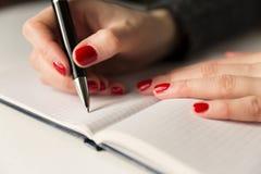 Manos femeninas con la escritura de la pluma en el cuaderno Diario, planes, periodista fotos de archivo libres de regalías