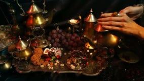 Manos femeninas con la joyería oriental que hace té en la taza Dulces marroquíes tradicionales Taza de té de la leche de Masala d