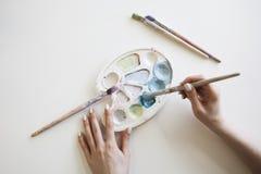 Manos femeninas con la paleta y los cepillos coloridos Fotografía de archivo