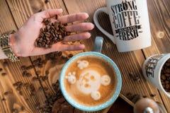Manos femeninas con los granos de café, una taza de café con espuma al lado de la amoladora de café en la tabla de madera, visión Imagen de archivo libre de regalías