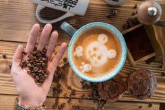 Manos femeninas con los granos de café, una taza de café con espuma al lado de la amoladora de café en la tabla de madera, visión Imágenes de archivo libres de regalías
