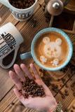 Manos femeninas con los granos de café, una taza de café con espuma al lado de la amoladora de café en la tabla de madera, visión Foto de archivo libre de regalías