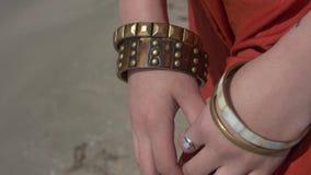 Manos femeninas con un anillo en un finger y en pulseras del color de bronce almacen de video