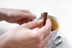 Manos femeninas con un chocolate y una taza de té fotos de archivo