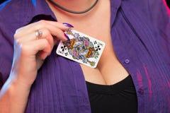 Manos femeninas con una manicura p?rpura sostener una cubierta de las tarjetas del juego fotografía de archivo