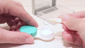 Manos femeninas cosechadas que sacan las lentes de contacto de un envase almacen de video