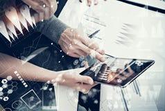 Manos femeninas de la foto que sostienen la pantalla táctil moderna de la tableta y del hombre Equipo de Businessmans que trabaja Imagen de archivo libre de regalías