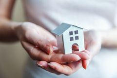 Manos femeninas de la mujer que sostienen la casa blanca miniatura del juguete foto de archivo