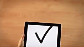 Manos femeninas de la visión superior que dibujan símbolo de la marca de verificación en la tableta digital almacen de video