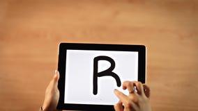 Manos femeninas de la visión superior que escriben la letra de B en la tableta digital metrajes