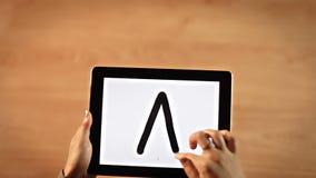 Manos femeninas de la visión superior que escriben la letra de A en la tableta digital metrajes