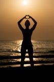 Manos femeninas de las siluetas que hacen una forma del corazón Imágenes de archivo libres de regalías