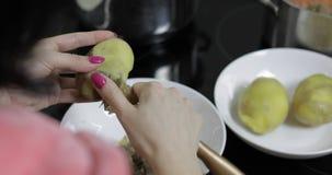 Manos femeninas del ama de casa que pelan las patatas en la cocina imagen de archivo