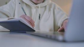 Manos femeninas del cuaderno de la tabla de la mujer del primer que se sientan que teclean el ordenador portátil usando el perno  almacen de metraje de vídeo