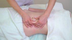 Manos femeninas del masajista que hacen masaje anti de las celulitis en el abdomen de la mujer joven almacen de metraje de vídeo