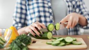 Manos femeninas del primer que tajan el pepino orgánico fresco usando el cuchillo que cocina la ensalada sana de la comida almacen de metraje de vídeo