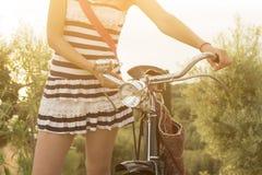 Manos femeninas en el manillar de la bicicleta Imagen de archivo libre de regalías