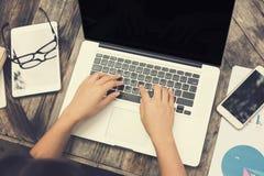 Manos femeninas en el teclado del ordenador portátil con otra tableta del ordenador encendido Fotos de archivo libres de regalías
