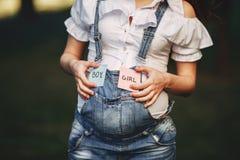 Manos femeninas en el vientre con con las tarjetas del MUCHACHO y de la MUCHACHA Imagenes de archivo