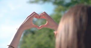 Manos femeninas en la forma del corazón sobre la naturaleza verde y el cielo azul Fotografía de archivo libre de regalías