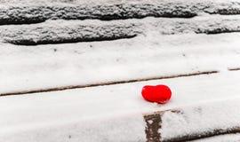 Manos femeninas en manoplas blancas hechas punto con el corazón de la nieve en día de invierno imagen de archivo libre de regalías