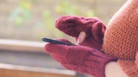 Manos femeninas en manoplas usando el teléfono elegante almacen de metraje de vídeo