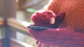 Manos femeninas en manoplas usando el teléfono elegante almacen de video