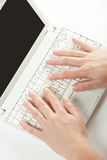 Manos femeninas en un teclado de la computadora portátil Fotos de archivo