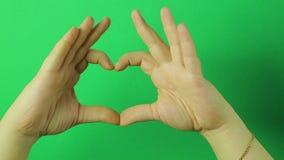 Manos femeninas en una demostración verde del fondo una muestra del corazón de la emoción del amor Primer almacen de video